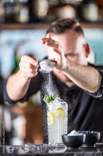 Fotografía  Professional barman making  alcoholic cocktail drink with fruits sugar and herbs