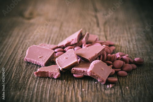 Fotografía  Broken and shattered pieces of ruby red chocolate in a round charcoal stone ceramic bowl