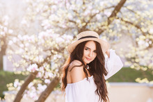 Outdoor Close Up Portrait Of Young Beautiful Happy Smiling Woman With Long Dark Hair, Makeup, Wearing Straw Hat, White Blouse, Posing Near Blooming Tree. Copy, Empty Space For Text