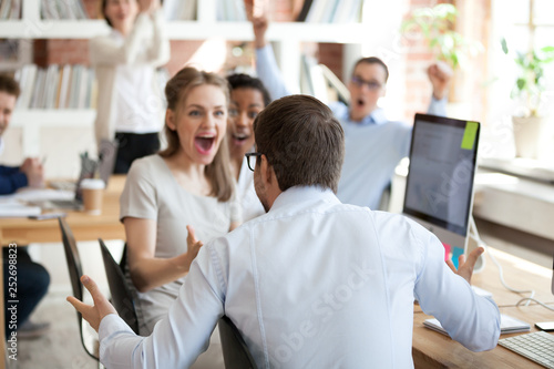 Diverse business people celebrating victory sitting in shared office Canvas Print