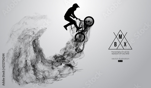 Photo Abstract silhouette of a bmx rider on the white background from particles, dust, smoke, steam