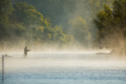 Photographie Men fishing in river with fly rod during summer morning