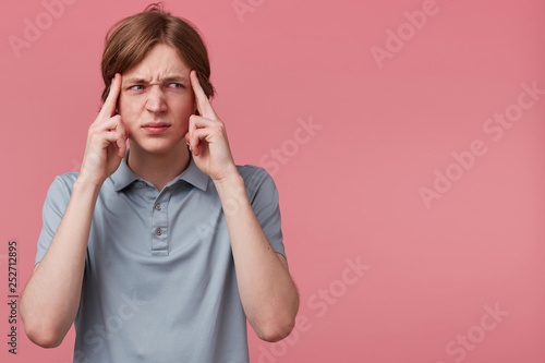 Photo Close up young man thinking, trying hard to remember something looking focused to the rightside on blank copyspace, fingers on temples isolated pink background