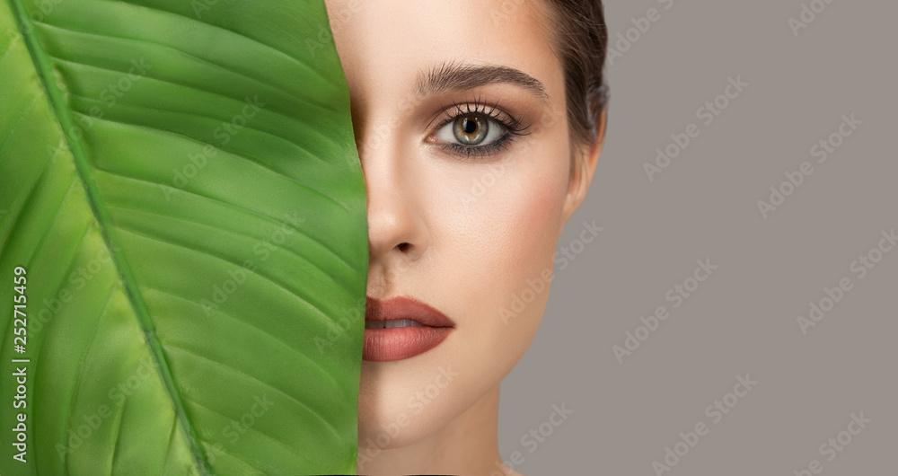 Fototapeta Portrait of woman and green leaf. Organic beauty. Gray background.