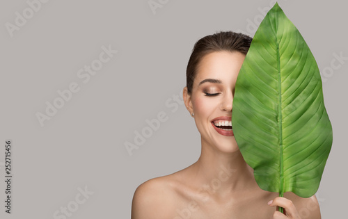 Obraz Portrait of woman and green leaf. Organic beauty. Gray background. - fototapety do salonu