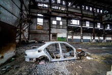 Side View Of An Old Rusty Antique Car Frame On The Background Of Broken-down Plant. Interior Of The Large Abandoned Building With A Damaged Car