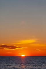 jasne pomarańczowe słońce z odbiciem w wodzie podczas zachodu słońca nad morzem