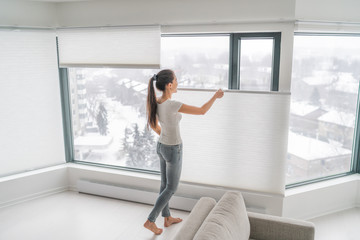 FototapetaWoman opening home curtains in urban condo. Modern top down bottom up privacy cellular shades on apartment window keeping heat in winter with honeycomb blind curtain. Cordless pleated shades.
