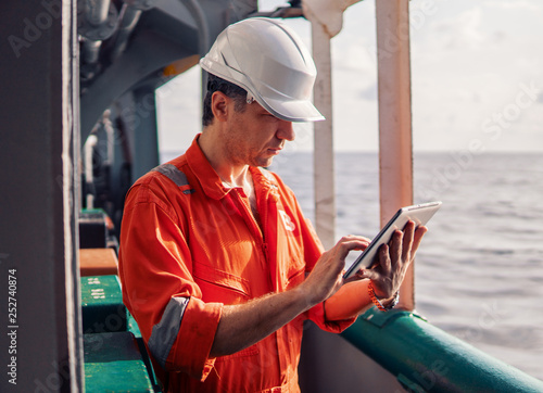 Marine chief officer or captain on deck of vessel or ship watching