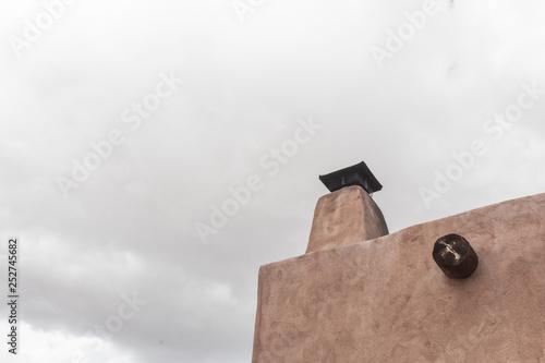 Foto  Exterior of traditional adobe building with chimney, viga, overcast sky, copy sp