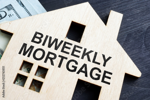 Biweekly mortgage. Wooden model of house and money. Canvas Print
