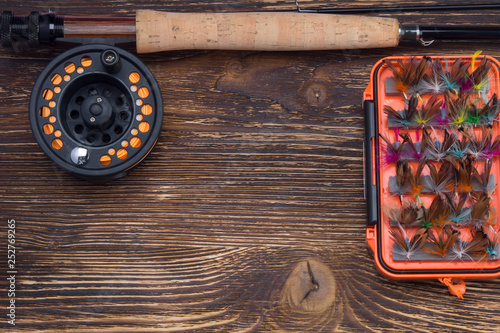 Fotografía  fishing rod with a reel and a set of bait, mosquitoes, butterflies and moths, on