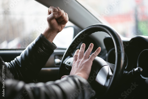 Fotografía Angry driver is honking and is yelling by sitting of a steering wheel
