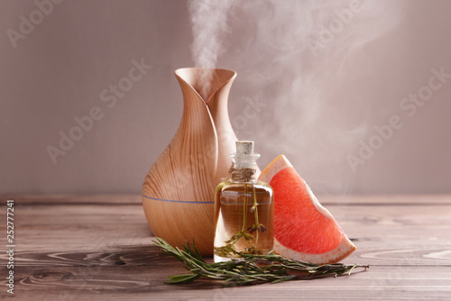 Fényképezés Aroma oil diffuser, rosemary and grapefruit on table