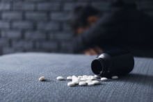 Overturned Bottle With Pills And Depressed Man On Background. Suicide Awareness Concept