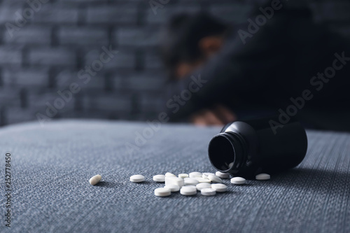 Overturned bottle with pills and depressed man on background Canvas Print