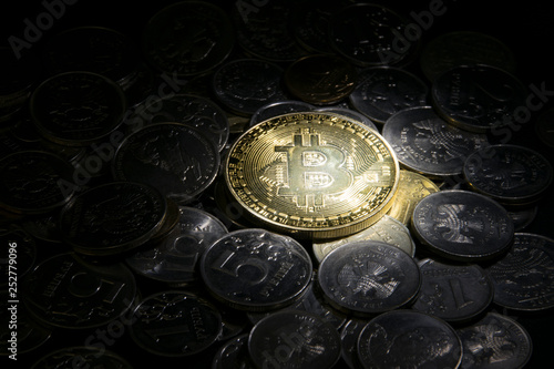 gold bitcoin coin on top on other coins in the beam  light