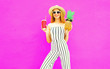 Leinwanddruck Bild - Happy smiling woman with pineapple, cup of juice in summer round straw hat, white striped jumpsuit on colorful pink wall background