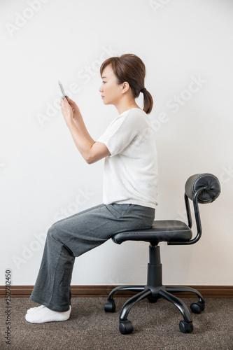 Photographie  姿勢よくスマホを見る女性