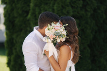 Man Kiss Woman And Hide By Bouquet. Wedding Day
