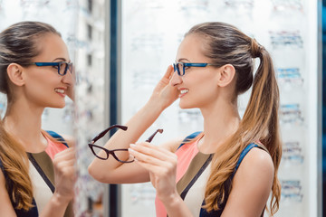 FototapetaYoung woman in optometrists store checking her looks in mirror