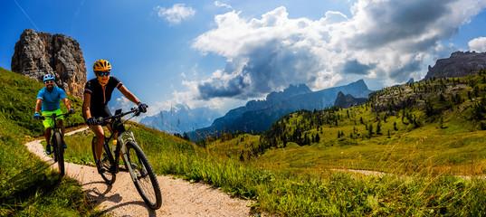 Vožnja biciklom žena i muškaraca na biciklima u krajoliku planina Dolomiti. Par biciklističkih MTB enduro staza. Sportske aktivnosti na otvorenom.