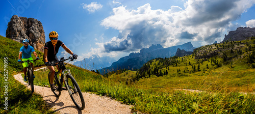 Fotografia  Cycling woman and man riding on bikes in Dolomites mountains landscape