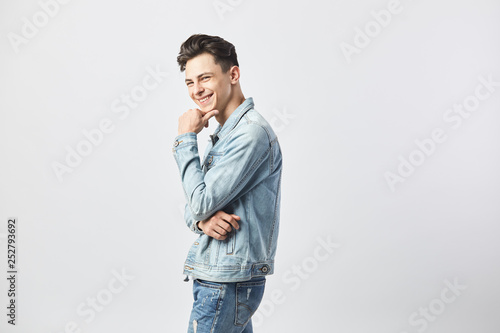 Photographie  Smiling dark-haired guy dressed in a white t-shirt and a denim jacket stands on