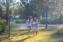 Child Playing With Garden Sprinkler. Kids Run And Jump. Summer Outdoor Water Fun In The Backyard