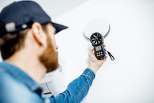 Handyman Checking The Speed Of Air Ventilation With Measuring Tool On The White Wall Background