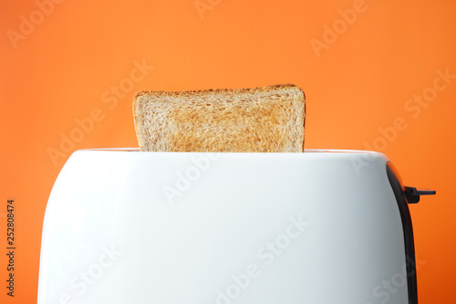 Photo  Slice of bread with toaster on color background