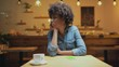 beautiful sad african american female customer propping chin with hand while waiting for someone in cafe