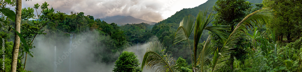 Fototapeta Aerial over Sekumpul waterfall surrounded by dense rainforest and mountains shrouded in mist at sunrise, Bali, Indonesia panoramic