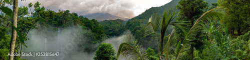 Aerial over Sekumpul waterfall surrounded by dense rainforest and mountains shro Fototapet