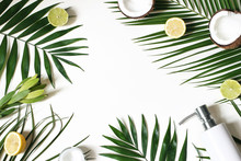 Styled Beauty Frame, Web Banner. Skin Cream, Soap Bottle, Coconut, Lemons And Lime Fruit On Lush Palm Leaves. White Table Background. Cosmetics, Spa And Tropical Summer Concept. Flat Lay, Top View.