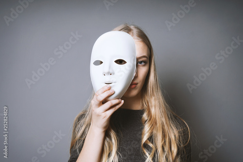 teen girl hiding her face behind mask - identity or personality concept Wallpaper Mural