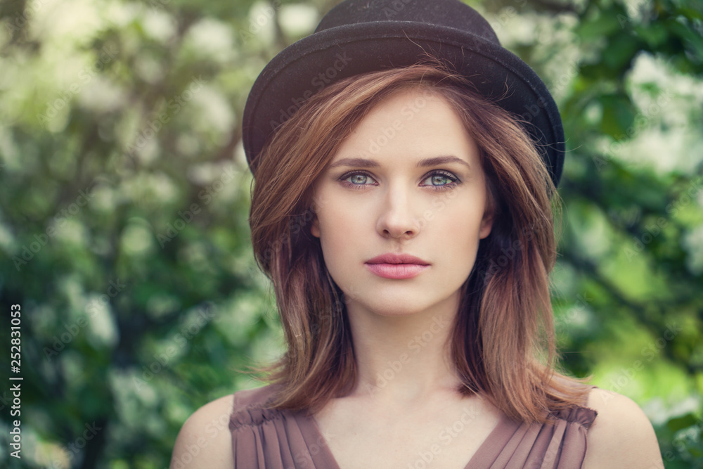 Fototapety, obrazy: Woman face closeup outdoor portrait. Pretty girl in hat on greenery foliage background