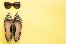 Sunglasses And Trendy Leopard Print Shoes On Pastel Yellow Background, Summer Fashion Concept. Top View, Selective Focus