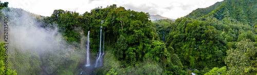Obraz Aerial over Sekumpul waterfall surrounded by dense rainforest and mountains shrouded in mist at sunrise, Bali, Indonesia panoramic - fototapety do salonu
