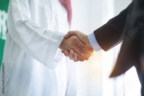 Photo Arabian businessman hands shaking with Asian businessman in office, business con