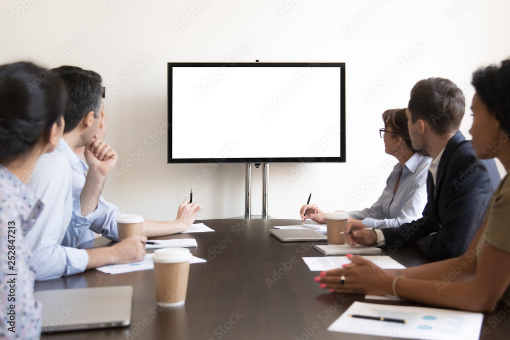 Fototapeta Business people group sitting at conference table looking at screen