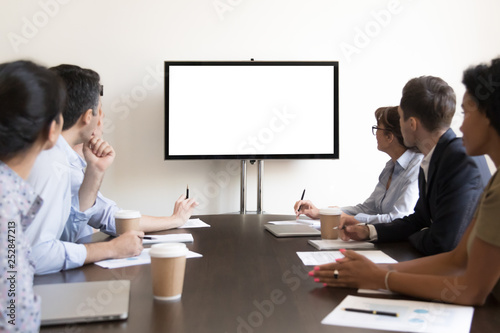 Obraz Business people group sitting at conference table looking at screen - fototapety do salonu
