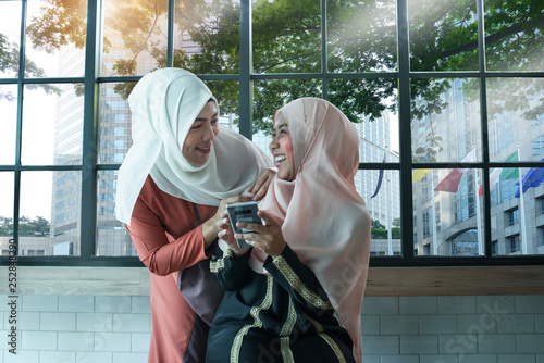 Fotografía  Muslim women wear hijab interested and fun with something in intelligent media,