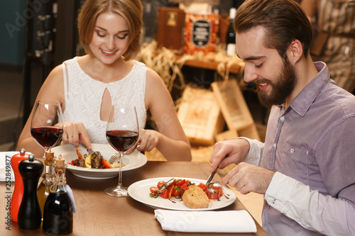 Tuinposter Restaurant Sharing tasty memories. Cheerful young couple having dinner at the local restaurant