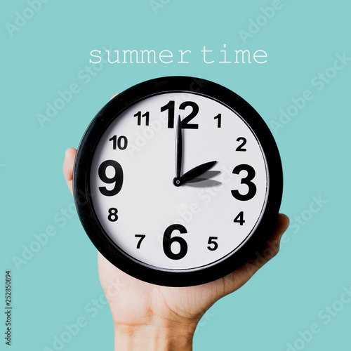 text summer time and clock being adjusted one hour