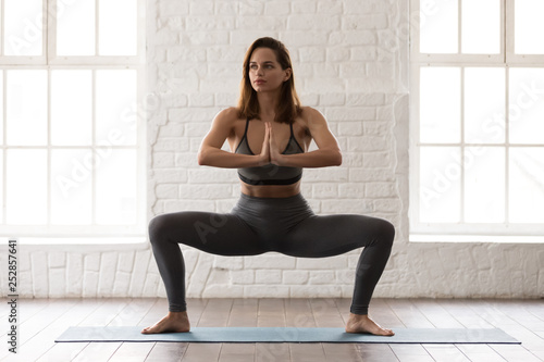 Fotomural  Attractive young woman practicing yoga, standing in Sumo Squat, Goddess