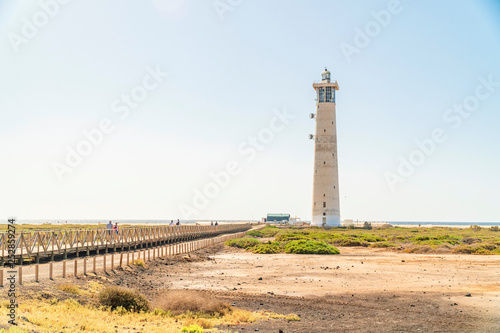 Fotografia  Lighthouse and wooden bridge with tourists in Morro Jable, Fuerteventura, Spain