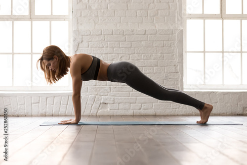 Woman practicing yoga, Push ups or press ups exercise, Plank