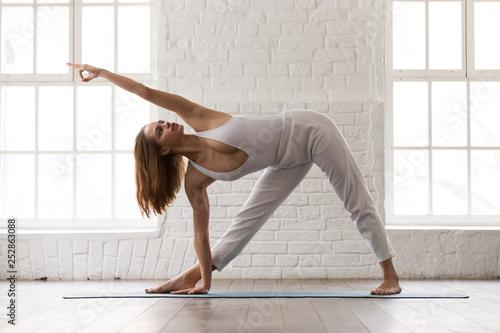 Woman practicing yoga, standing Utthita Trikonasana pose, extended triangle