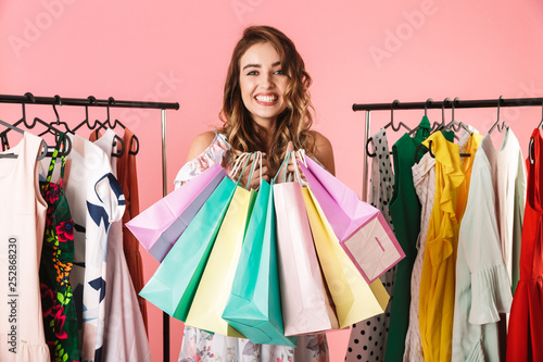 Fotomural  Photo of cute girl standing in store near clothes rack and holding colorful shop